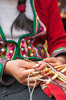 Quechua woman works a loom used to make textiles, Cusco Peru, South America