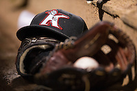 A Kannapolis Intimidators cap sits on top of a glove in the visitors dugout during the game against the Hickory Crawdads at L.P. Frans Stadium on April 23, 2015 in Hickory, North Carolina.  The Crawdads defeated the Intimidators 3-2 in 10 innings.  (Brian Westerholt/Four Seam Images)
