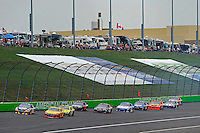 Martin Truex Jr., (#56) and Sam Hornish, Jr. (#22) leads a pack up the back straight.