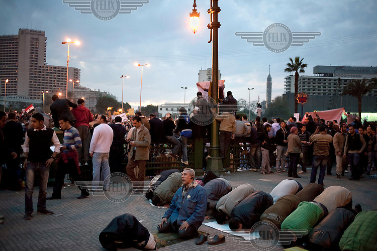 Men pray amidst a protest in Tahrir Square. Continued anti-government protests take place in Cairo calling for President Mubarak to stand down. After dissolving the government, Mubarak still refuses to step down from power.