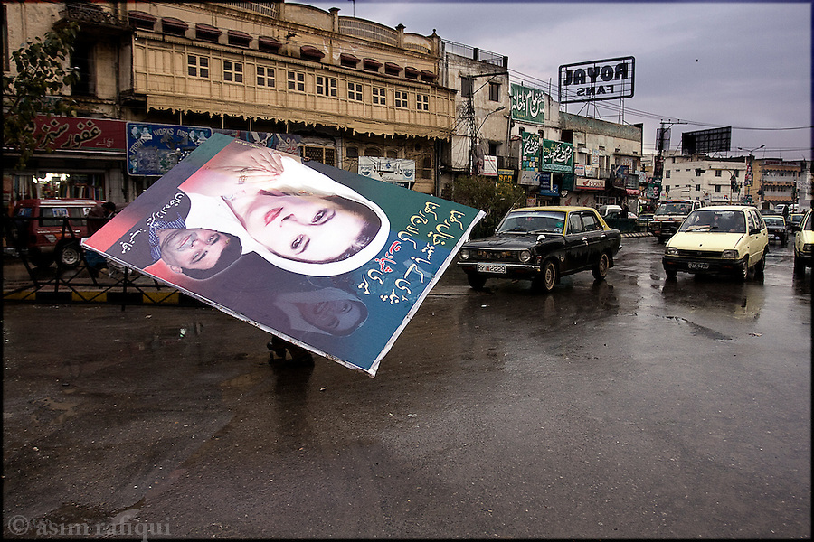 a Pakistan People's Party (PPP) worker carries a political poster prior to the February 18th elections - Benazir's assasination is expected to help the PPP gain a strong position