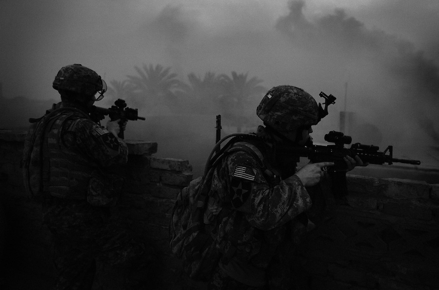 Wreathed in smoke from a smoke grenade meant to give Apache attack helicopters circling overhead a fix on their position, soldiers with Alpha Co. 2-12 Infantry 2nd Infantry Division scan the rooftops from insurgents after their platoon took sniper fire during a patrol in the Dora section of south-central Bagdhad on Thursday May 10, 2007.