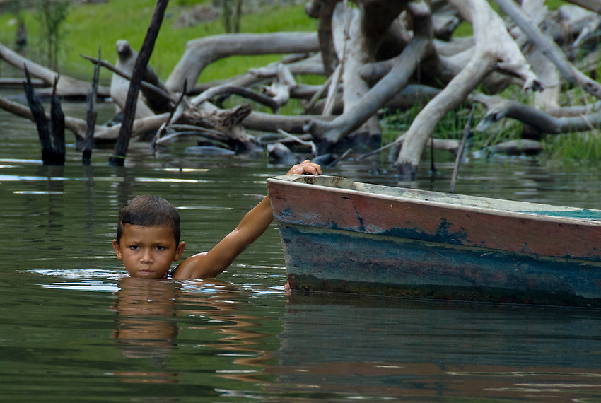 Boy swimming in the Amazon River, holding on to a canoe.