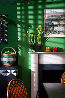 In a modern dining room, the walls are in bold Fennel Green by Sanderson and decorated with stencils by fashion textile designer Sarah Pasricha.