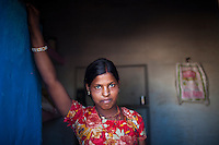 Nitu (not her real name), stands for a portrait at her home in Jhaju village, Bikaner, Rajasthan, India on 4th October 2012. Now 18, she was married off at age 10 to a boy of around the same age, but only went to live with her in-laws when she was 12, after she had finished studying up to class 6. The three sisters, aged 10, 12, and 15 were married off on the same day by their maternal grandfather while their father was hospitalized. She was abused by her young husband and in-laws so her father took her back after hearing that her husband, who works in a brick kiln, was an alcoholic and was doing drugs and crime. She had only spent a few days at her husband's house at that time. Her father (now out of the hospital) has said that she will only be allowed to return to her husband's house if he changes his ways but so far, the negotiations are still underway. Photo by Suzanne Lee for PLAN UK