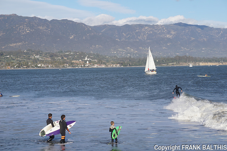 Surfing and sailing at the Santa Barbara Harbor Jetty