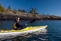 A female sea kayaker paddles the rugged shoreline of Lake Superior at Isle Royale National Park.
