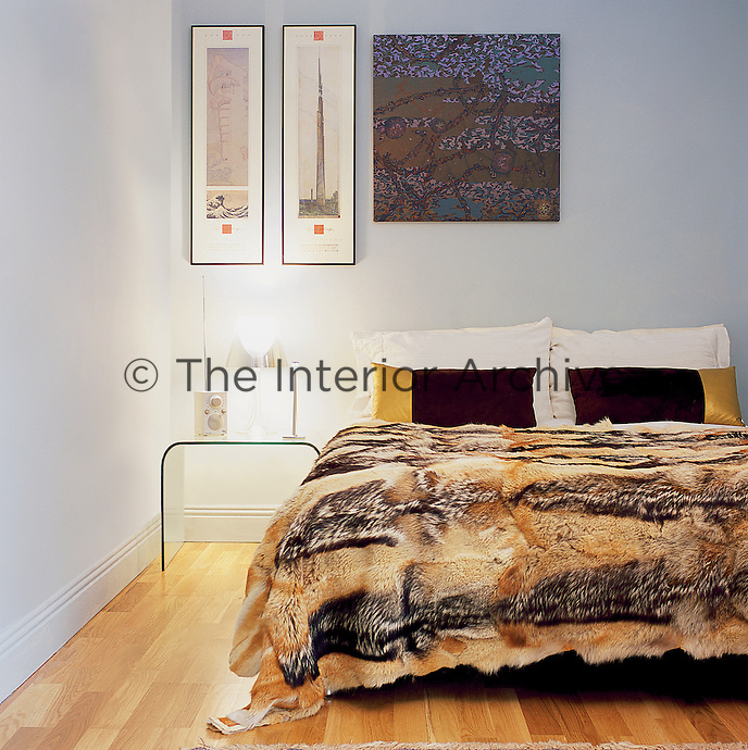 A light blue bedroom with an oak floor. A chrome lamp stands on a perspex Ligne Roset bedside table and the bed has a fur blanket,