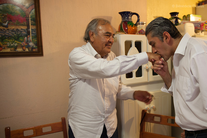 "Donovan kisses his father's hand while celebrating his 43rd birthday at his home in Texcoco, Mexico on May 9, 2015. Donovan Tavera, 43, is the director of ""Limpieza Forense México"", the country's first and so far the only government-accredited forensic cleaning company. Since 2000, Tavera, a self-taught forensic technician, and his family have offered services to clean up homicides, unattended death, suicides, the homes of compulsive hoarders and houses destroyed by fire or flooding. Despite rising violence that has left 70,000 people dead and 23,000 disappeared since 2006, Mexico has only one certified forensic cleaner. As a consequence, the biological hazards associated with crime scenes are going unchecked all around the country. Photo by Bénédicte Desrus"