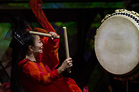 A woman performer wearing red plays a taiko drum during a Mangekyo performance by Wadaiko group, DRUM TAO in Lumine 0 theatre, Shinjuku, Tokyo, Japan, Friday November 16th 2018. The Mangekyo  performance includes koto and shamisen music along with traditional  and contemporary taiko drumming and acrobatics. Organised by the Japan Tourist bureau (JTB) and the Japanese Government to entertain foreign visitors in readiness for the 2020 Tokyo Olympics. the performances run to the end of November and utilise state of the art projection mapping by TeamLab.