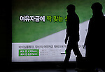Benchmark rate, Mar 12, 2015 : A worker (2nd R) walks as he installs a new board advertising new deposit interest of a bank in Seoul, South Korea. The Bank of Korea brought down the base rate to a record low of 1.75 percent on Thursday, according to local media.  (Photo by Lee Jae-Won/AFLO) (SOUTH KOREA)