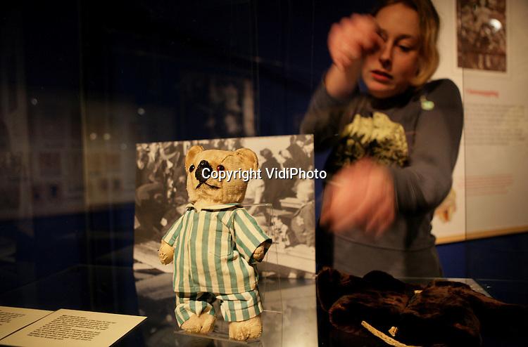 """Foto: VidiPhoto..GROESBEEK - Een medewerkster van het Nationaal Bevrijdingsmuseum in Groesbeek legt vrijdag de laatste hand aan een expositie over zelfgemaakt speelgoed van Joodse kinderen uit de Tweede Wereldoorlog. De tentoonstelling """"Geen Kinderspel"""" toont dat speelgoed voor kinderen belangrijk was en symbool stond voor overlevingskracht en troost. De expositie is afkomstig van het befaamde herinneringscentrum Yad Vashem in Jeruzalem en was daar een grote publiekstrekker. """"Geen Kinderspel"""" loopt van 27 februari tot en met 28 mei."""