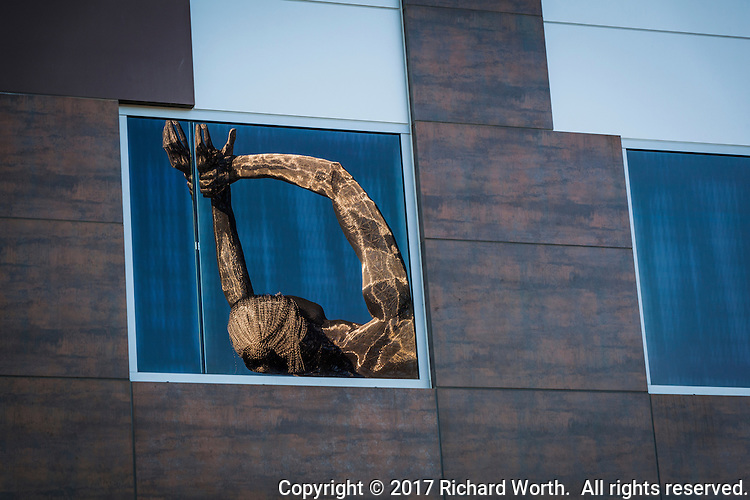"""Close-up of the reflection of the head and arms of the """"Truth is Beauty"""" sculpture at the San Leandro Tech Center"""