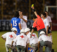 Yellow Card is issued while medics address injured El Salvador player during FIFA World Cup qualifier against El Salvador. USA tied El Salvador 2-2 at Estadio Cuscatlán Stadium in El Salvador on March 28, 2009.