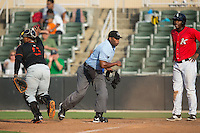 Delmarva Shorebirds catcher Yermin Mercedes (8) shows the ball as home plate umpire Christopher Lloyd calls Alexander Simon (23) of the Kannapolis Intimidators out at home plate at CMC-Northeast Stadium on June 7, 2015 in Kannapolis, North Carolina.  The Shorebirds defeated the Intimidators 9-1.  (Brian Westerholt/Four Seam Images)