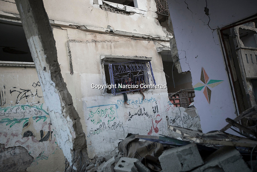 """In this Saturday, Aug. 16, 2014 photo, Palestinian children play at a window house damaged by airstrikes and artillery shelling during the """"Protective Edge"""" Israeli military operation in Beit Hoanoun neighborhood in Gaza City. After a five days truce was declared on 13th August between Hamas and Israel, civilian population went back to what remains from their houses and goods in Gaza Strip. (Photo/Narciso Contreras)"""
