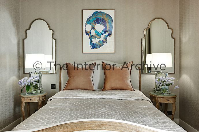 A traditional bedroom with neutral wallpaper. Lamps stand on decorative bedside tables either side of a French style double bed with an upholstered head and footboard. A modern painting of a blue skull contrasts with the traditional decor.