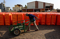 BURKINA FASO , Bobo Dioulasso, Société Burkinabè des Fibres Textiles SOFITEX cotton ginning company unit Bobo III, processing of conventional and gene manipulated Monsanto BT cotton, bales are ready for Export wrapped in orange plastic cover / SOFITEX, Fabrik fuer Baumwollentkernung Werk Bobo III, Verarbeitung von konventioneller und genmanipulierter Monsanto Baumwolle, Ballen in Plastikfolie fertig fuer den Export