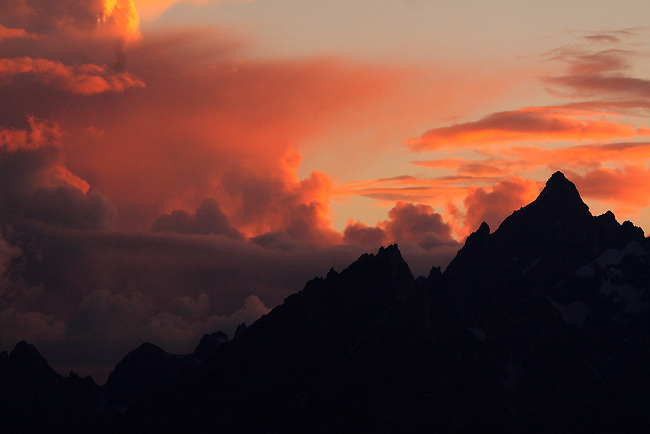 THE SUN SETS AMONGST A BAND OF CLOUDS WITH THE GRAND TETON PROVIDING A SILHOUETTE AT GRAND TETON NATIONAL PARK,WYOMING