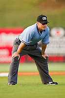 Umpire Mike Cascioppo handles the calls on the bases during the South Atlantic League game between the Greensboro Grasshoppers and the Kannapolis Intimidators at Fieldcrest Cannon Stadium on June 19, 2011 in Kannapolis, North Carolina.  The Intimidators defeated the Grasshoppers 9-7.   (Brian Westerholt / Four Seam Images)