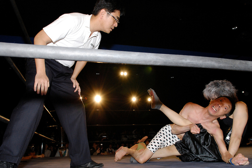 """Orochi"" and ""E.T."" grapple  as referee Shinsuke Funabashi watches."