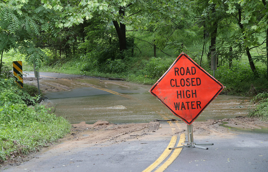 A road closed sign cautions drivers as flood waters flow over Carpenters Mill Road Friday in Greene County. Photo/Andrew Shurtleff Photography, LLC
