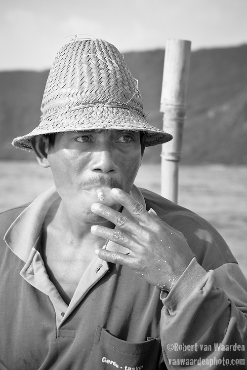 Syria, a fisherman from Kuta, Lombok, Indonesia, takes a smoke break. Syria fishes everyday, quite often accompanied by his son, Sunardi. Typically they will catch 30 - 50 small fish per outing. These will be sold at the market and they live on approximately 7 dollars US a month.