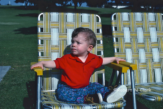 Young boy sitting in lawn chair in the park looking for someone with an exasperated look on his face