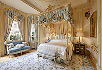 An opulent bedroom with a four poster bed with an ornate gilt top. The room is decorated in blue and white. A small settee is placed in front of a window dressed with gold and blue striped curtaining