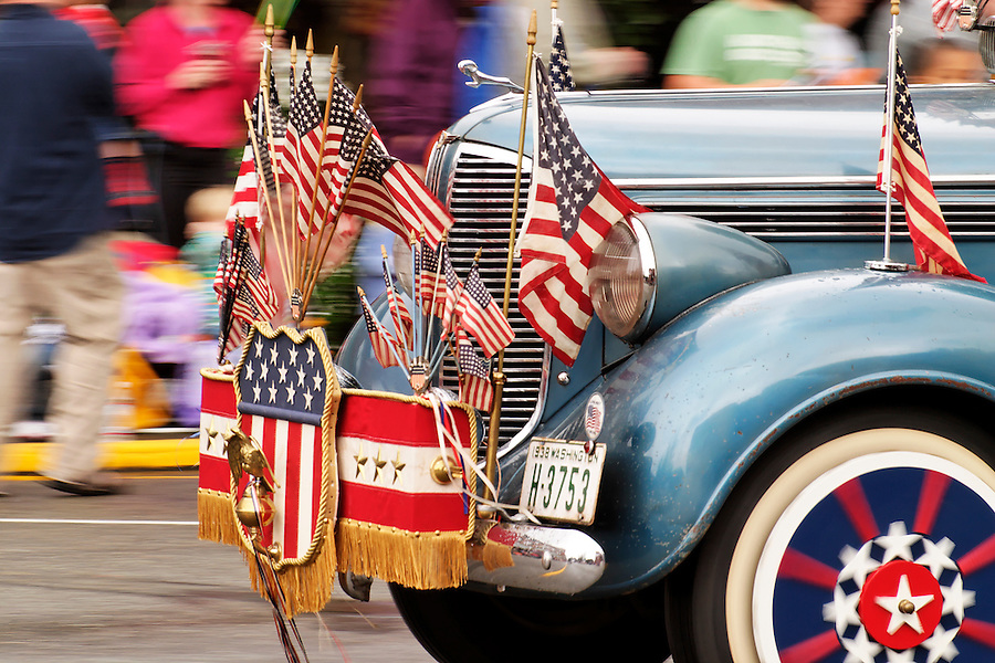 Classic car adorned with US flags and regalia driving in parade to celebrate Kla Ha Ya Days, Snohomish, Snohomish County, Washington, USA