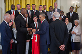 United States President Barack Obama, with Vice President Joseph Biden (L), receives a jersey from Thurl Bailey (2-L) after greeting former players and staff of the 1983 NCAA National Basketball Championship North Carolina State Wolfpack in the East Room of the White House in Washington, DC, USA, 09 May 2016. The President and Vice President met briefly with members of the team and their families in the East Room. The team was previously unable to visit the White House to be recognized for their championship.<br /> Credit: Shawn Thew / Pool via CNP