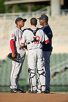 Greenville Drive pitching coach Walter Miranda (right) has a meeting on the mound with pitcher Jose Almonte (29) and catcher Austin Rei (13) during the game against the Kannapolis Intimidators at Intimidators Stadium on June 8, 2016 in Kannapolis, North Carolina.  The Intimidators defeated the Drive 3-2.  (Brian Westerholt/Four Seam Images)