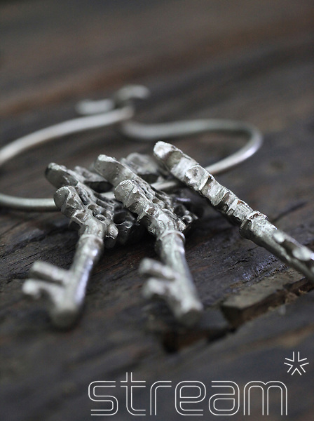 Three silver keys attached to a large silver ring. Dark wooden textured table.