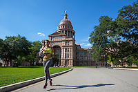 Healthy fit urban African American woman running at the Texas Capitol grounds, wearing earphones and listening to music on a sunny day with blue skies in downtown Austin, Texas.  The Texas State Capitol grounds are a favorite place for runners with many running trails and roads and round the clock security providing a safe environment for joggers and runners - stock image.