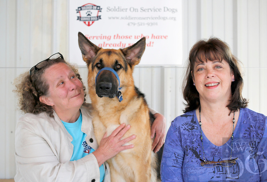 NWA Democrat-Gazette/DAVID GOTTSCHALK  Scout, a one year old service dog in advance training, sits with Elise Burt (right), veterans program manager, and Angie Pratt, executive director, Thursday, May 19, 2016, at the Soldier On Service Dogs facility in Fayetteville.