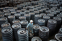 A worker inspects stacks of train wheels at the Wheel and Tyre Plant of Ma Steel (Maanshan Iron & Steel Co.) in Maanshan, Anhui Province, China. The plant is the largest producer of train wheels in China..