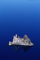 Aerial view of a rock formation created by lava rises in contrast above the blue water. Crater Lake National Park, Oregon.