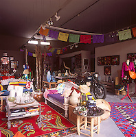 A cluttered living room where a collection of eclectic items are arranged and grouped together as though in a shop display.