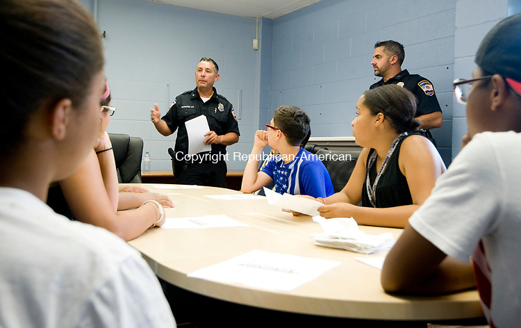 TORRINGTON, CT-071817JS03--Torrington police officer Anthony Pietrafesa, left, and officer Rob Simon, right,  talks with students who are participating in the Teen Outreach Program at the Connecticut junior Republic, Tuesday at the newly opened Torrington Police Department's community outreach office at Coe Memorial Park Civic Center. Officer Pietrafesa was organizing help for the PAL and Family Strides Inc. annual Kids Day which will be held Thursday at Best Park Pool. <br />  Jim Shannon Republican-American