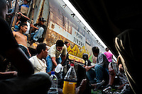 """Central American immigrants, sitting under the stopped cargo train, wait to climb it up again when it departs to cross the state of Chiapas in the south of Mexico, on 25 May 2010. Between 2010 and 2015, the US and Mexico have apprehended almost 1 million illegal immigrants from El Salvador, Honduras, and Guatemala. While the economic reasons remain the most frequent motivation for people from Central America to illegally immigrate to the US, thousands of Salvadorans, Guatemalans, and Hondurans, many of them minors, seek asylum in the US due to the thriving crime and gang-related violence in their region (known as the Northern Triangle). Taking an exhausting and risky journey, riding thousands of miles atop the cargo trains, facing a physical danger and extortion from the organized crime groups that control migrant routes, the """"undocumented"""" still flee to the US, looking for their American dream."""