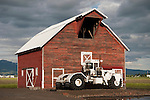 Self-propelled floater sprayer by a weathered red wooden barn near La Grande, Ore.