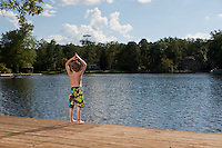 Little boy standing on the edge of a summertime dock and looking out onto a public lake