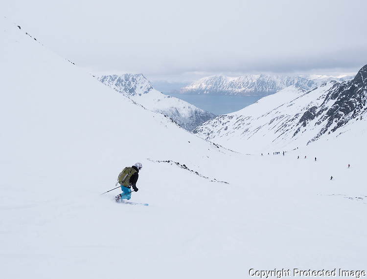 Skiløpere på vei ned Ringaruta fra Øksfjordjøkelen mot Tverrfjord. ---- Skiers decending Ringaruta from Øksfjordjøkelen glacier.