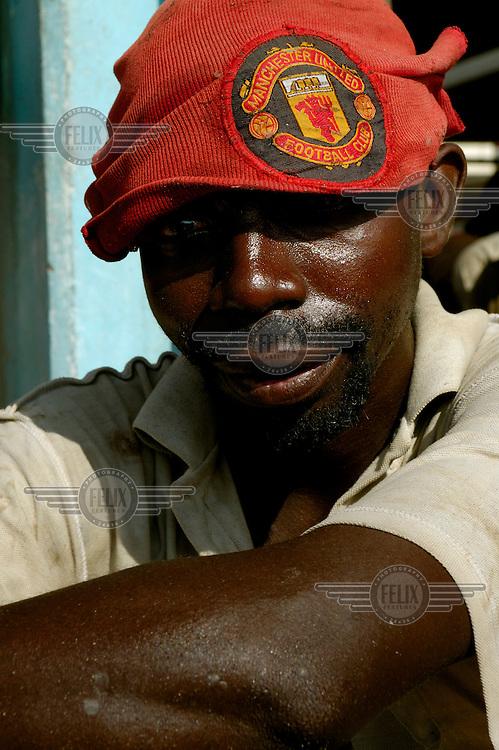 Man with a Manchester United football cap at the city's Magogoni fish market.