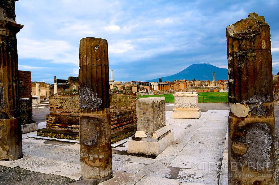 Broken columns in Pompeii with Vesuvius rising in background