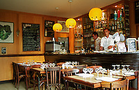 Inside Cafe de l'Esperance in Bouliac. Typical French traditional cafe restaurant. Wooden tables chairs, wine glasses and napkins on the tables. On the wall a chalkboard blackboard chalk black board with the menu, two waiters at the bar preparing for lunch. Bordeaux Gironde Aquitaine France Europe