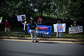 Demonstrators hold signs as United States President Donald J. Trump's motorcade leaves Trump National Golf Club in Sterling, VA USA, 7 September  2019.<br /> Credit: Zach Gibson / Pool via CNP