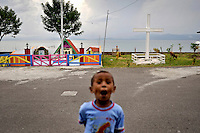 A child poses in front of a roadside shrine for the Tiberias Church along the Masohi waterfront. /Felix Features