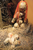 "Switzerland. Canton Tessin. Vira Gambarogno. The old town shows an exhibit of various Nativity scenes, illuminated at night for the Christmas holiday season. A Nativity Scene, may be used to describe any depiction of the Nativity of Jesus in art, but in the sense covered here, also called a crib or in North America and France a crèche (meaning ""crib"" or ""manger"" in French). It means a three-dimensional folk art depiction of the birth or birthplace of Jesus, either sculpted or using two-dimensional (cut-out) figures arranged in a three-dimensional setting. Christian nativity scenes, in two dimensions (drawings, paintings, icons, etc.) or three (sculpture or other three-dimensional crafts), usually show Jesus in a manger, Joseph and Mary in a barn (or cave). Sculture of the Vigin Mary and Jesus. © 2007 Didier Ruef"