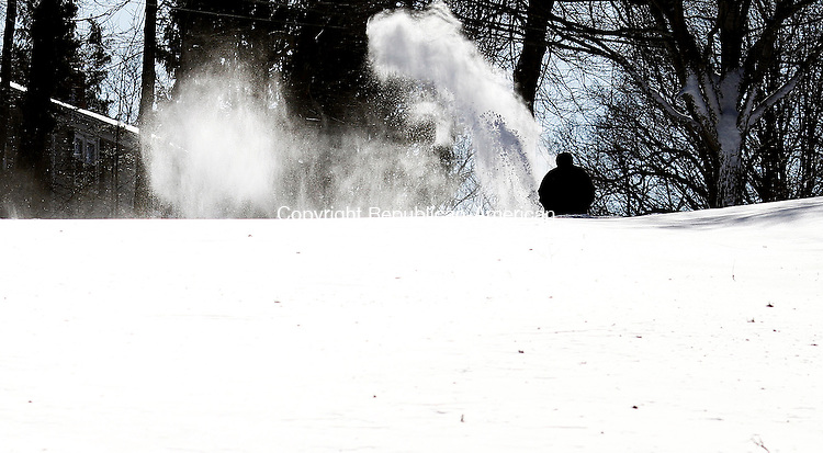 Naugatuck, CT- 09 February 2013-020913CM07- A man snow blows the end of a driveway as Deepwood Road in Naugatuck remained unplowed Saturday afternoon.  Residents were digging themselves out after a blizzard dumped more than two feet of snow in the area.   Christopher Massa Republican-American